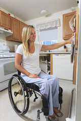 Woman with spinal cord injury in her accessible kitchen
