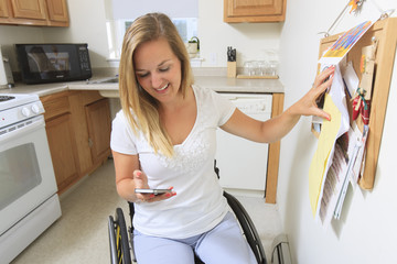 Woman with spinal cord injury looking at her mobile phone