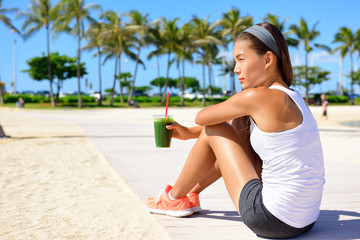 Healthy woman runner drinking green smoothie