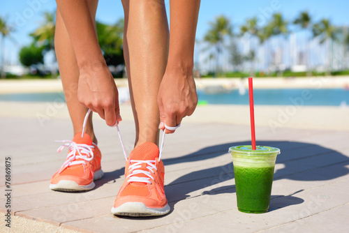 Running woman runner with green vegetable smoothie - 76869875