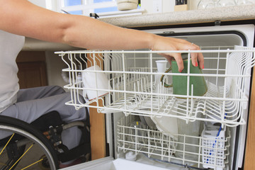 Woman with spinal cord injury putting a cup in the dishwasher