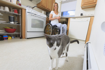 Woman with spinal cord injury with her cat in accessible kitchen
