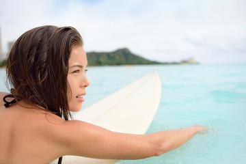 Surfer girl surfing paddeling on surfboard