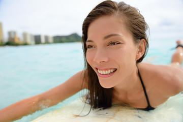 Surfer girl surfing on Waikiki Beach Hawaii