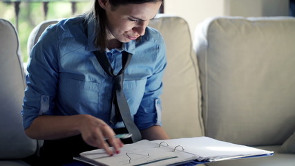businesswoman with documents sitting on sofa at home