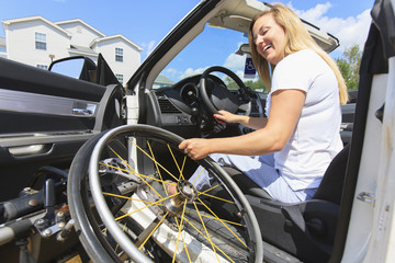 Woman with spinal cord injury lifting wheelchair into car