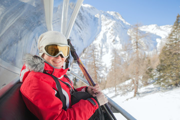 The smiling woman sits at chair lift on mountain resort