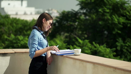 businesswoman writing notes in documents standing on terrace
