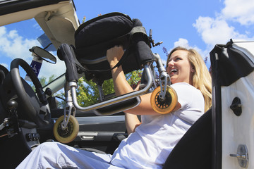 Woman with spinal cord injury lifting her wheelchair into car