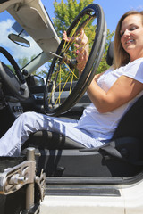 Woman with spinal cord injury lifting wheel into vehicle