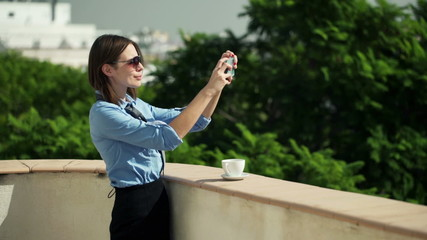 businesswoman taking selfie with cellphone on terrace