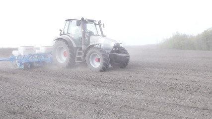 Tractor with planter sows black boundless field clouseup