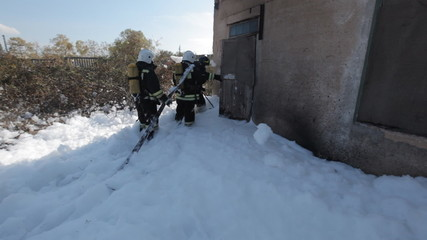 Firefighters in gas masks are in the foam