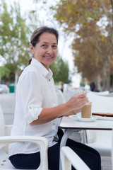 mature woman sitting  in  cafe