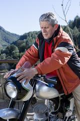 man caressing a motorbike.