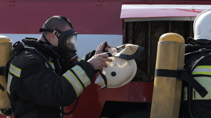 Firefighters wear gas masks and uniforms while standing by fire