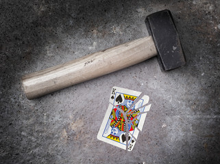 Hammer with a broken card, king of spades