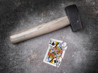 Hammer with a broken card, queen of spades