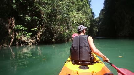 elderly man smile rowing kayak across sea water and looks around