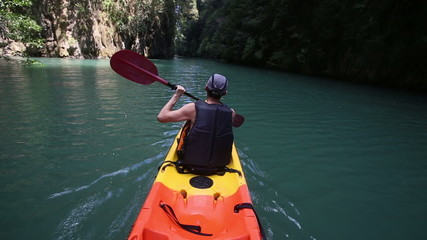 elderly man smile rowing kayak across sea water among rocks