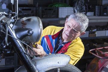 mechanic fixing the motorcycle headlight.