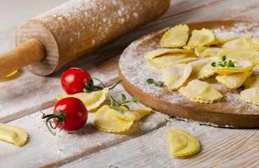 Ravioli on with flour  on  wooden backround.