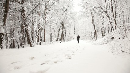 Man running in the forest during a winter day
