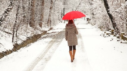 Woman with red umbrella walking in the park