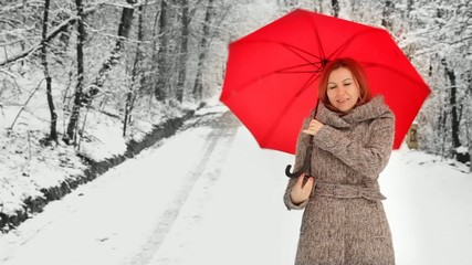 Woman playing with a red umbrella during winter in the park