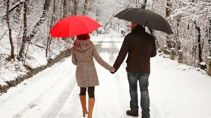 Couple holding hands walking during a winter day