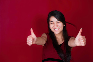 Beautiful biracial teen girl with thumbs up on red background