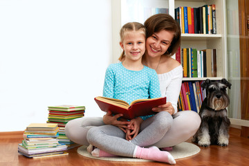 Mom reading a book her little daughter. beside them sitting dog