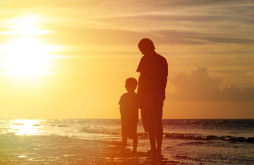 father and son holding hands at sunset