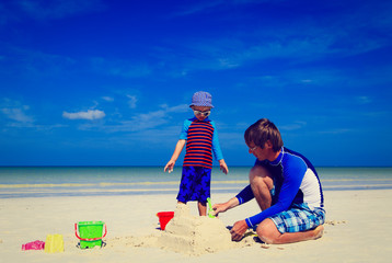 father and son building sand castle on tropical beach