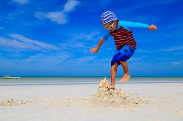 little boy jumping on the beach