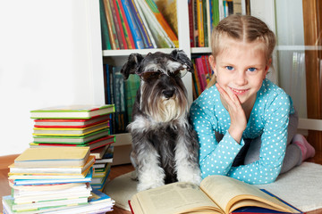 girl and her dog in glasses reading a book, sitting on floor in