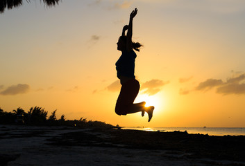 Silhouette of woman jumping on beach
