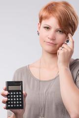 Junge rothaarige Frau mit Taschenrechner