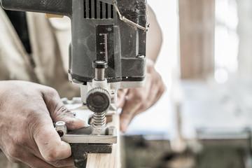 Blurred motion of carpenter working, preparing door for hinges
