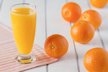 Fresh orange juice in a white wooden table with a napkin