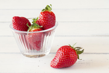 Bowl with strawberries on white wooden