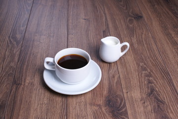Кружка  с чёрным кофе и молочник на деревянном столе