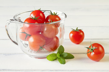 Red tomatoes and peppermint on white wooden table and cup