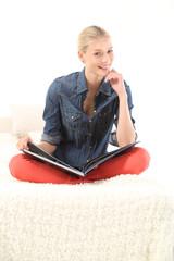 Junge Frau mit einem Buch auf dem Schoß