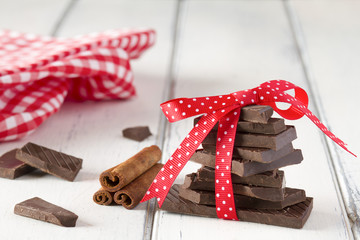 Stack of chocolate with a red ribbon and napkin on white table.