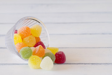 Colorful sweet jellies with sugar in a bowl on a white table