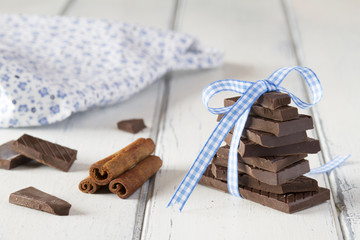 Stack of chocolate with a blue ribbon and napkin on white table
