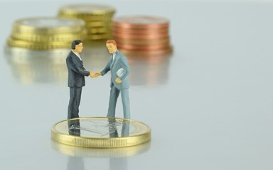 Miniature businessmen sealing a financial deal with a handshake