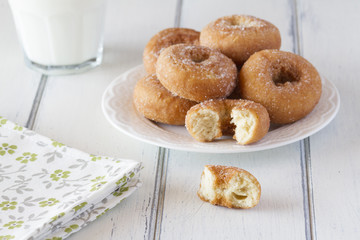 Breakfast with donuts and milk and a napkin on a white table