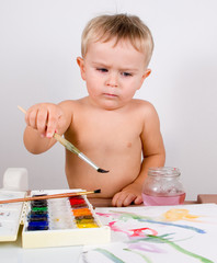 Little boy painting by aquarelle